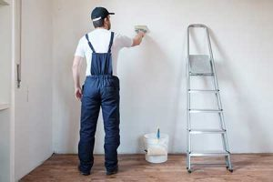 Man painting a wall with a paint bucket and ladder next to him.